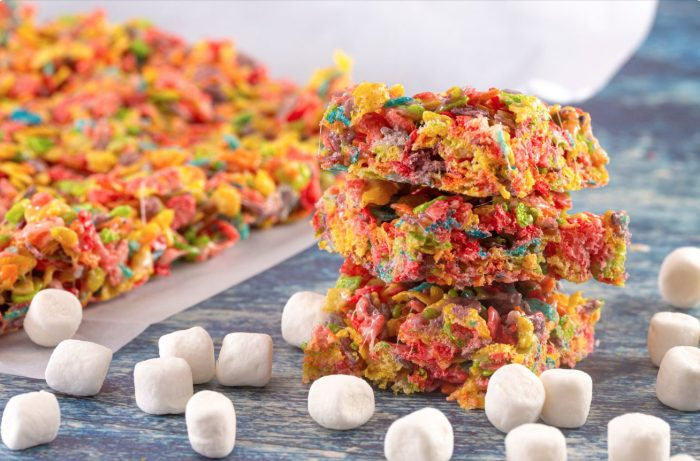 a stack of weed fruity pebble bars on a blue wooden table with marshmallows and more fruity pebble bars in the background
