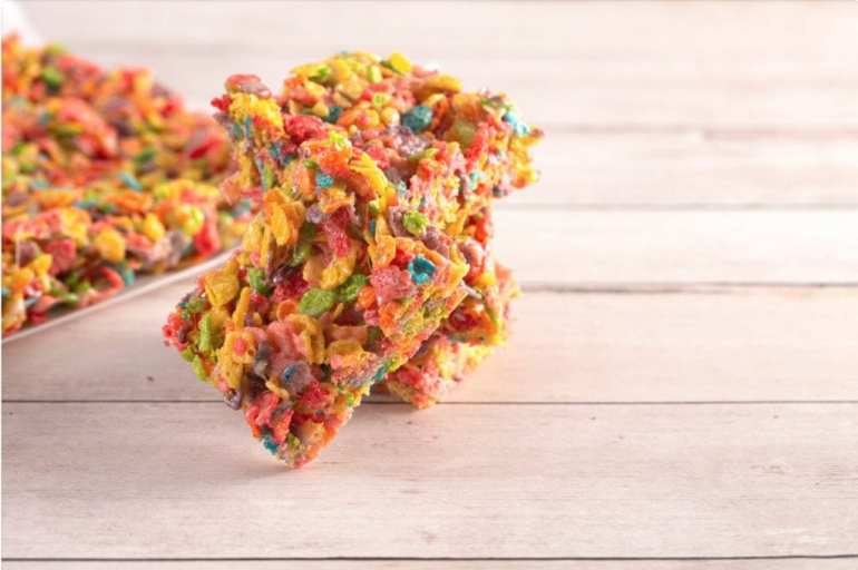 Macro of cannabis infused fruity pebble bars on a wooden table with more cereal bars in the background