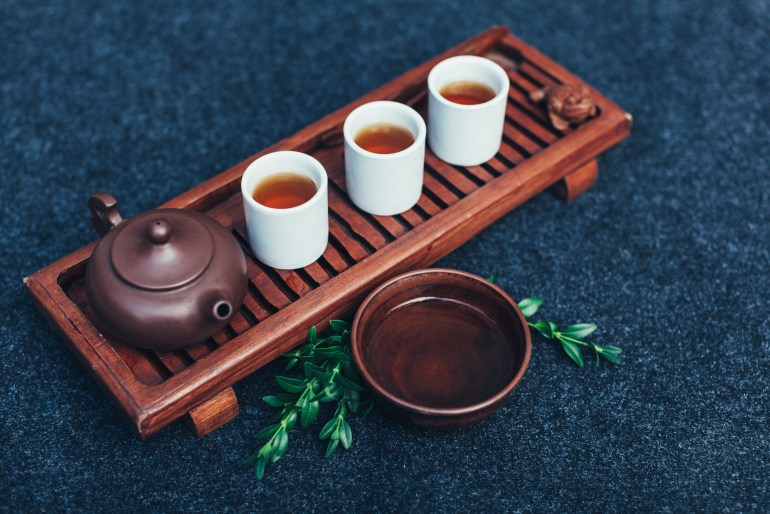 Traditional weed tea ceremony accessories. # glasses of cannabis tea on a wooden board with a clay pot beside them.