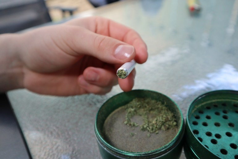 The end of a one hitter stamped with cannabis. The green grinder sits on the glass table beside it.
