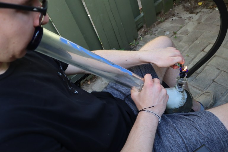 A male igniting a cannabis bowl from a glass bong.