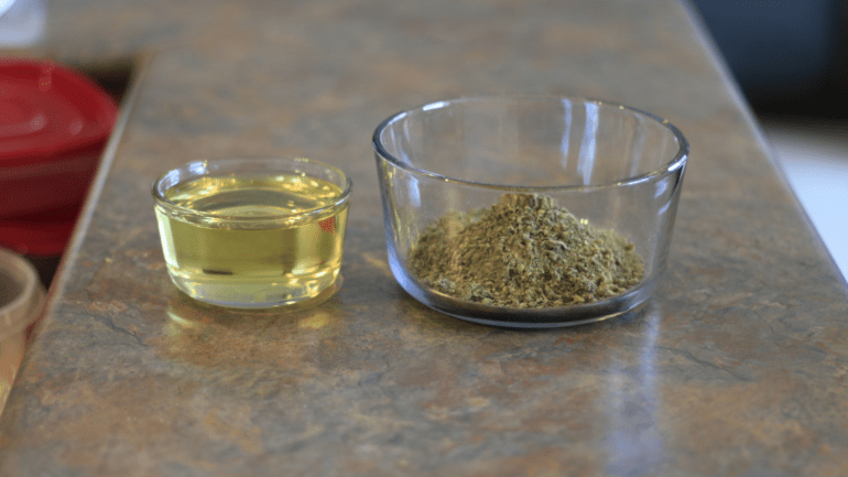 CBD-infused cooking oil that has a yellow colour to it, sits in a glass bowl on a counter top. A bow of ground weed sits beside it.