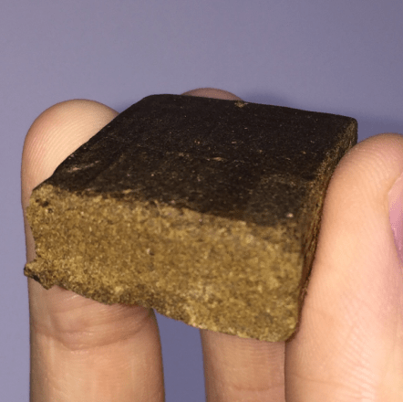 a man holds a brown square chunk of pressed hash in between his fingers.