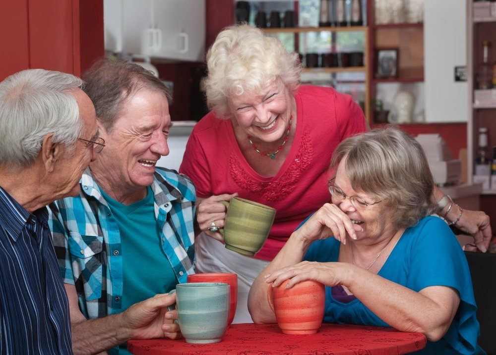 group of seniors laughing over coffee