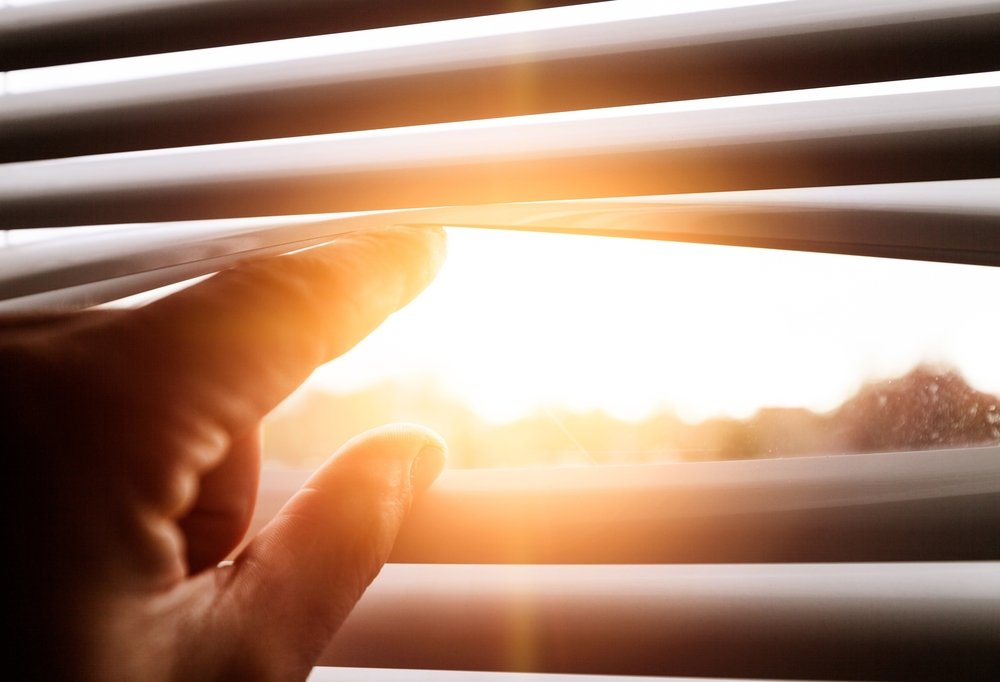 peering out at the scorching summer sun through window blinds