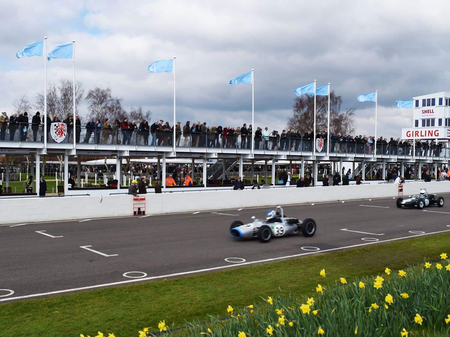 Cars race along the pit straight during practice for the Taylor Trophy at the 73rd Goodwood Members' Meeting