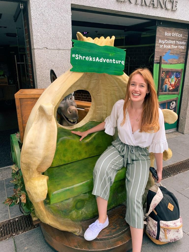 Travel blogger sat outside the Shrek museum on Southbank in London
