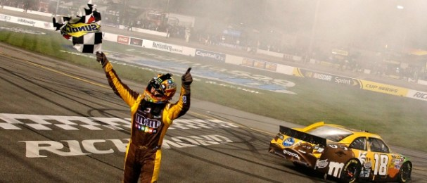Busch holds the checkered flag aloft follwing his victory (Photo Credit: Tom Pennington/Getty Images for NASCAR)