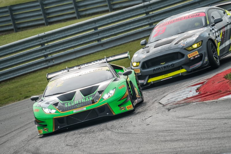 A Lamborghini and a Ford Mustang on a race track.