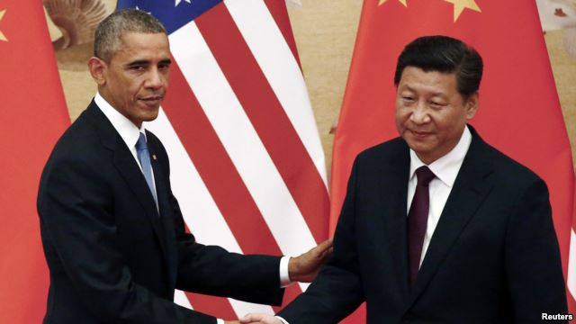 FILE - U.S. President Barack Obama, left, shakes hands with China's President Xi Jinping in front of U.S. and Chinese national flags during a joint news conference at the Great Hall of the People in Beijing, Nov. 12, 2014.