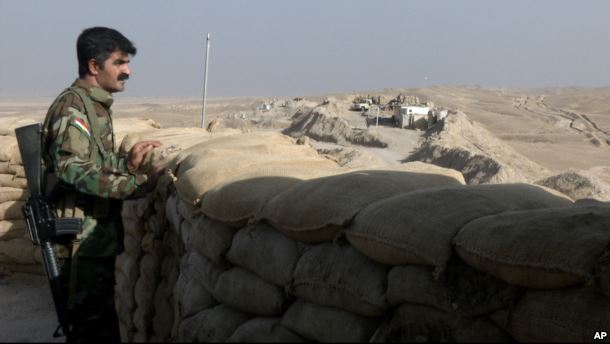 FILE - A militiaman of the Kurdistan Freedom Party, an Iranian Kurdish opposition group, looks over the sandbags at a section of the front line near the Iraqi city of Kirkuk, Sept. 5, 2016.