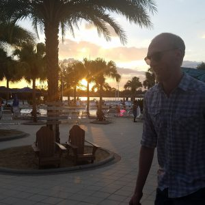 Christopher Morris walking down a sunset laden square in Florida.