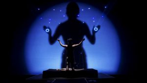 Image of a female performer silhouetted against a twinkling midnight blue backdrop, where a giant shadow looks back at her, circles of light like eyes in the palms of its hands