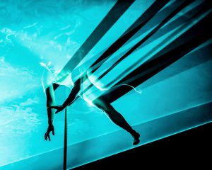 Photo from underneath a sheet of turquoise blue light. On the other side of the light curtain, the figure of aerial performer Aedín Walsh looks down. Her arms, one leg, and the tail of the vertical rope that holds her above the ground reach down through the light towards us, becoming black sihouettes, and casting shafts of diagonal black shadows out to the edges of the picture