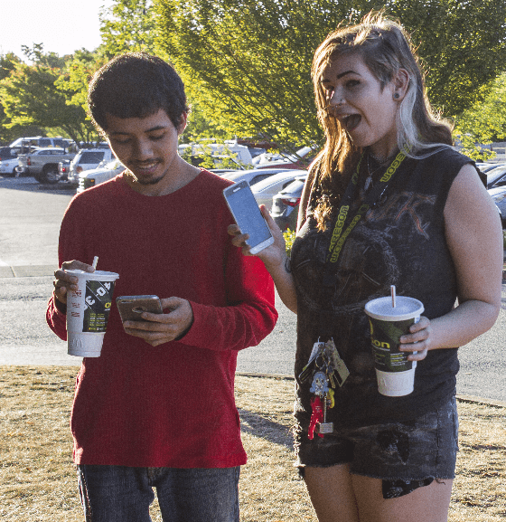 Jonathan Lopez and Megan Kunde play Pokémon Go near the Art Center.
