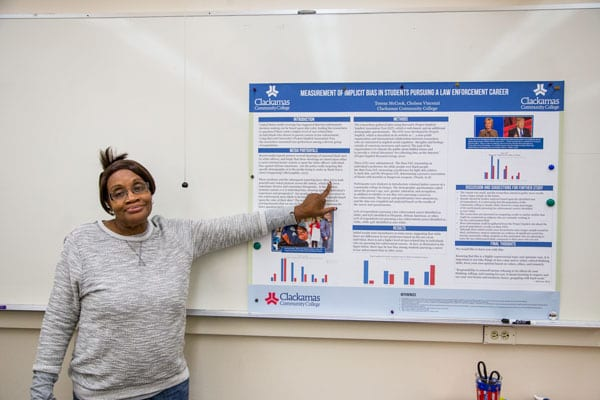 """Teresa McCook explains the poster, """"Measurement of Implicit Bias in Students Pursuing a Law Enforcement Career,"""" that won second place in the competition."""