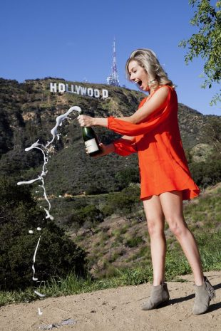 Sebrin Elms of The Clumsy Traveler popping champagne in orange dress in front of Hollywood sign, Los Angeles, California