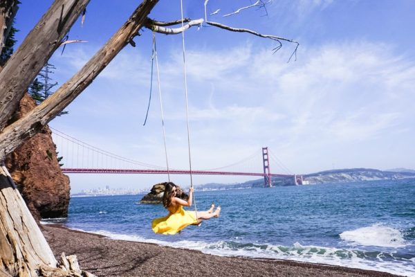 Meet Clumsy Traveler Christine; girl swinging in yellow dress San Francisco