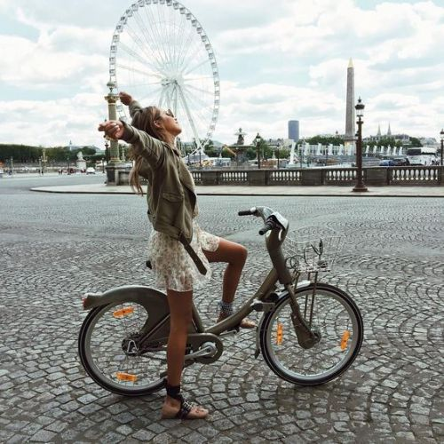 Travel When You Have a Bad Back; tourist girl stretch on bike in Paris France