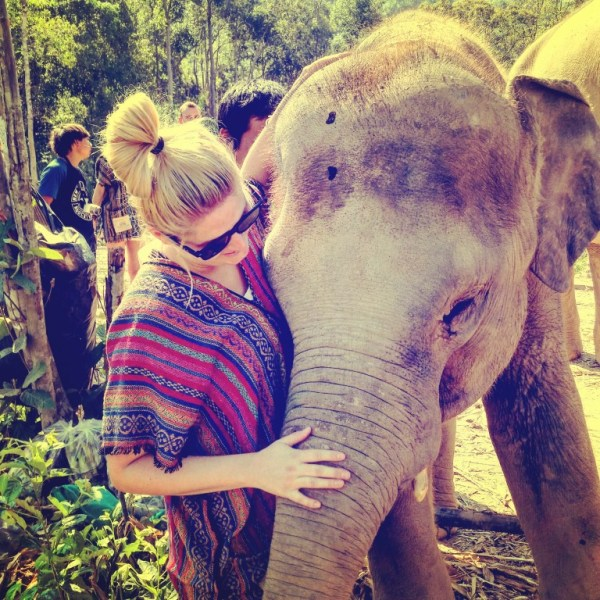 Meet Clumsy Traveler Chloe; blonde girl playing with elephant