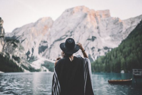 Travel When You Have a Bad Back; girl facing mountains and blue lake blake hat travel wanderlust