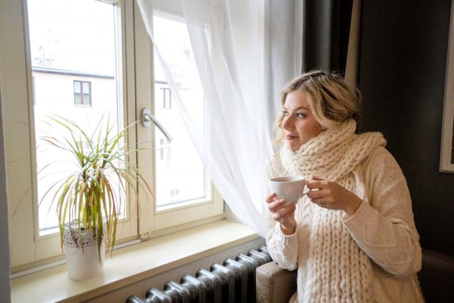 girl wearing chunky scarf looking out window with tea