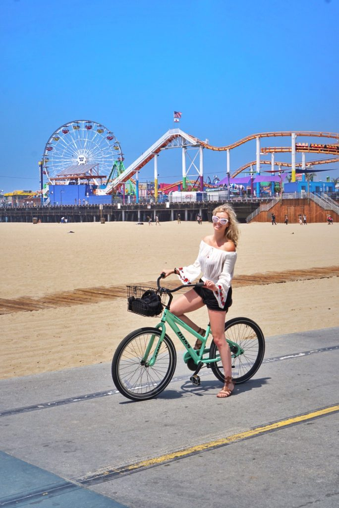 travel and reduce your carbon footprint; girl on bike santa monica pier