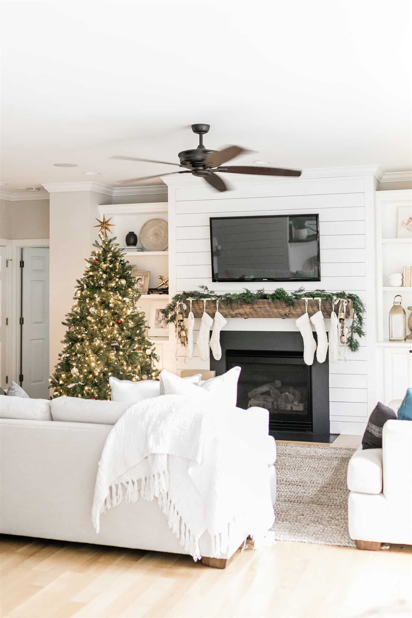 How to decorate your mantel for Christmas with simple garland, black and white striped ribbon, bells, and neutral stockings.  Also, a look at our Christmas decor from last year.  A simple and neutral Christmas decor inspiration post.  #neutralchristmas #christmasdecor #simplechristmas #christmasinspiration #cedargarland