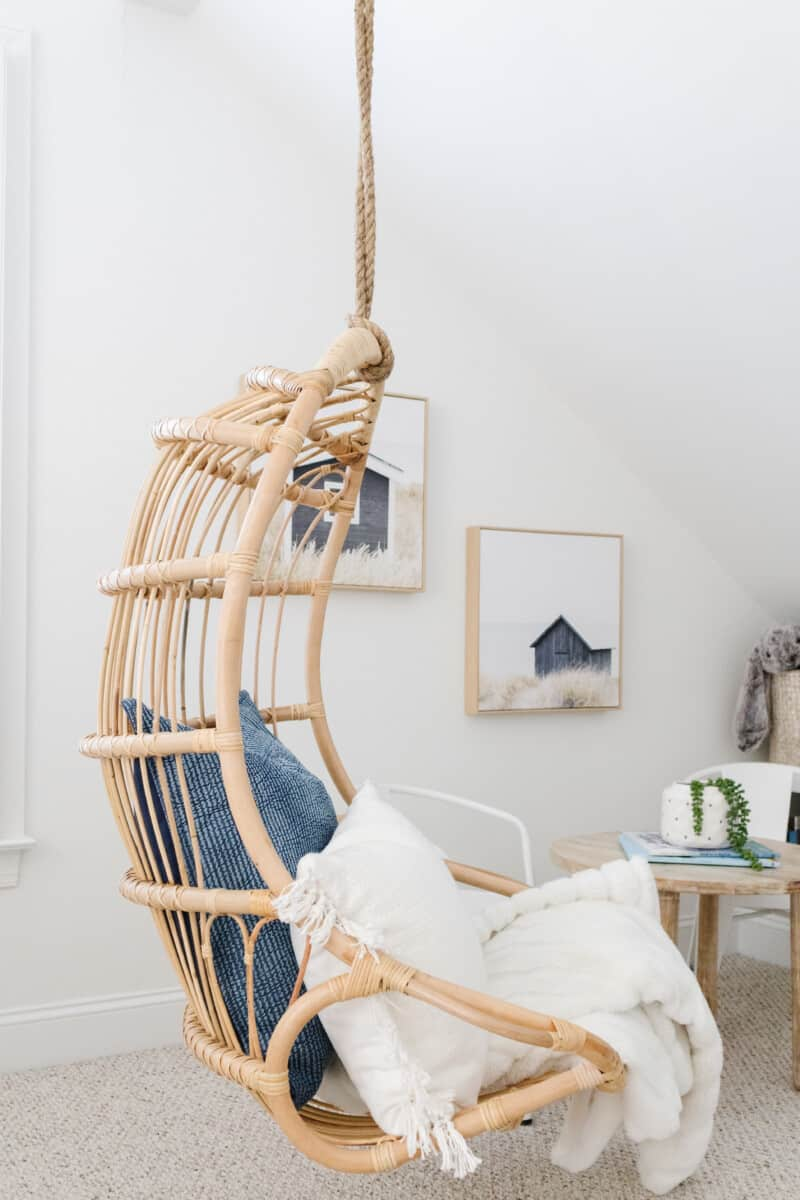 Coastal playroom inspiration with blue striped wallpaper, Serena & Lily hanging ratting chair, kid's table and bistro chairs, natural rug, brass wall sconces, and more.  #coastal #coastalplayroom #blueplayroom #coastalkidsroom #serenaandlily #serenaandlilychair #hangingchair #rattanchair #bluedecor