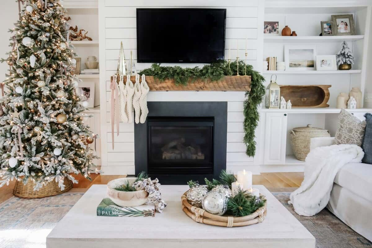Our simple and coastal living room decorated for Christmas, including a flocked christmas tree, cedar garland on the mantel, cedar wreaths on the French doors, and chic coffee table decor. #coastal #coastalchristmas #christmaswreath #wreaths #diychristmas #livingroom #christmaslivingroom #flockedchristmastree #simplechristmas #neutralchristmas