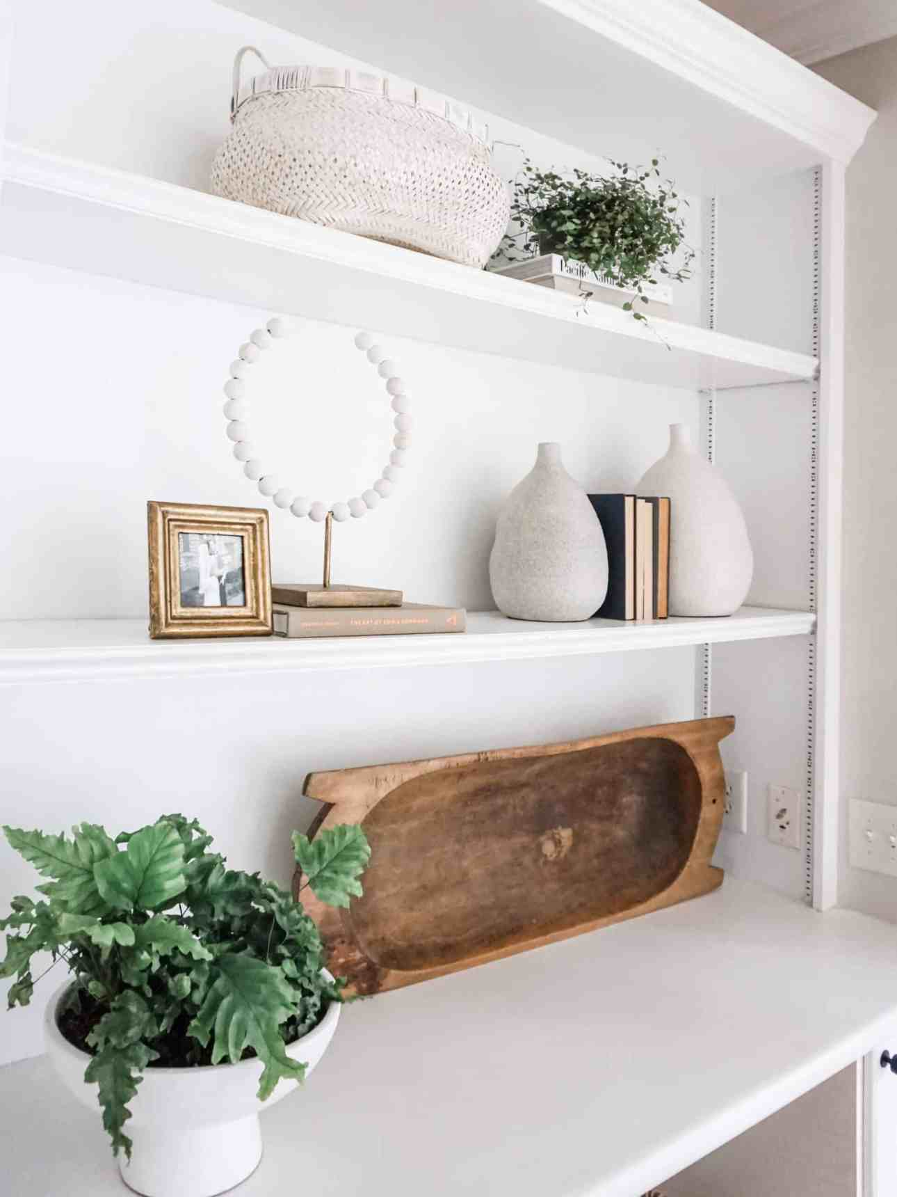 How to style a shelf like a pro, including tips for following the rule of three, adding plants to shelves, using books for shelf decor, and more.  How to create a cohesive design with builtins! #builtins #bookshelfstyling #shelfdecor #shelfstyling #builtins #bookcase #fireplacedecor #coastalbookcase #coastaldecor #neutralbookshelf #shelfie