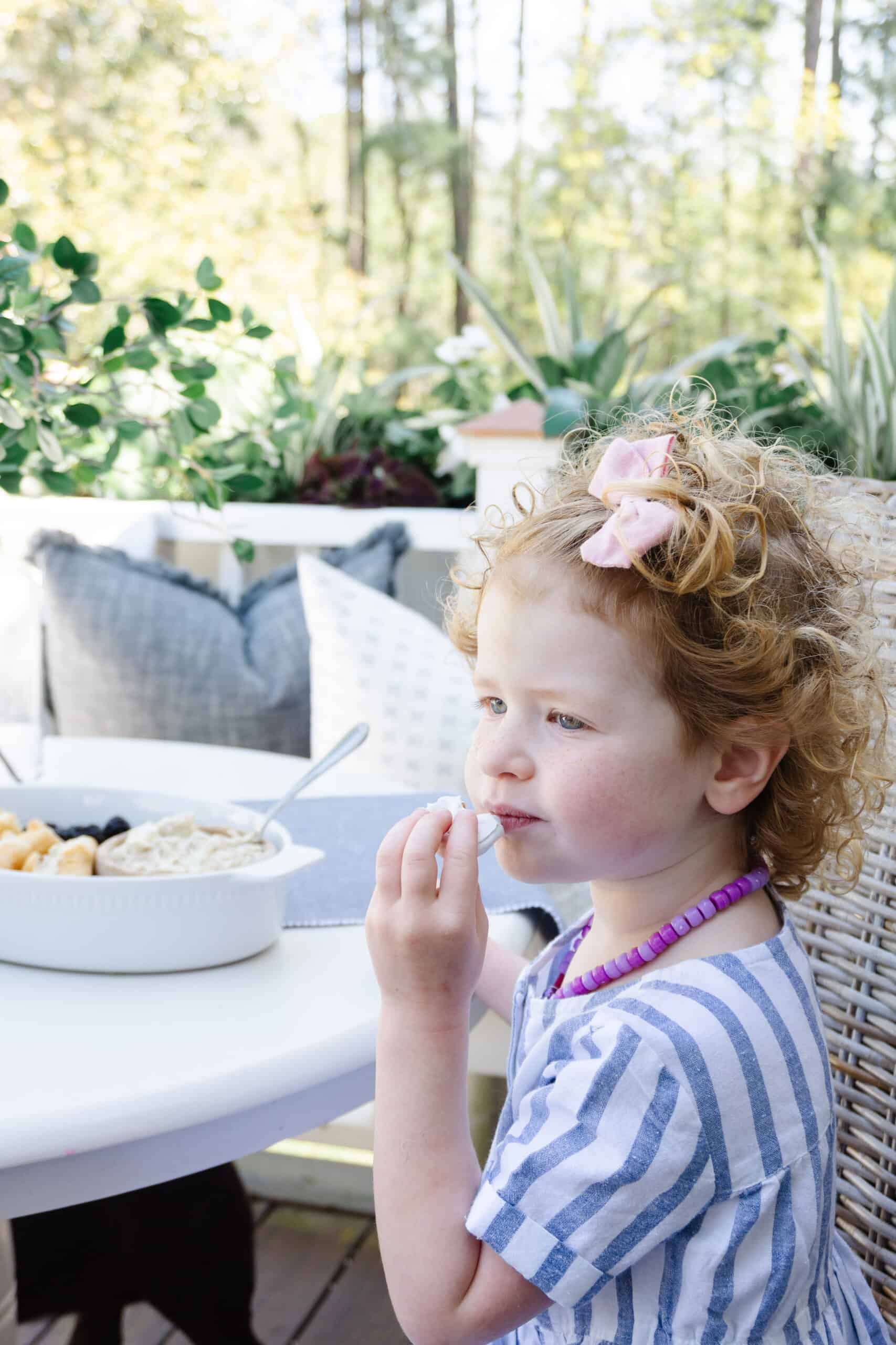 Toddler girl snacking on kids charcuterie board.