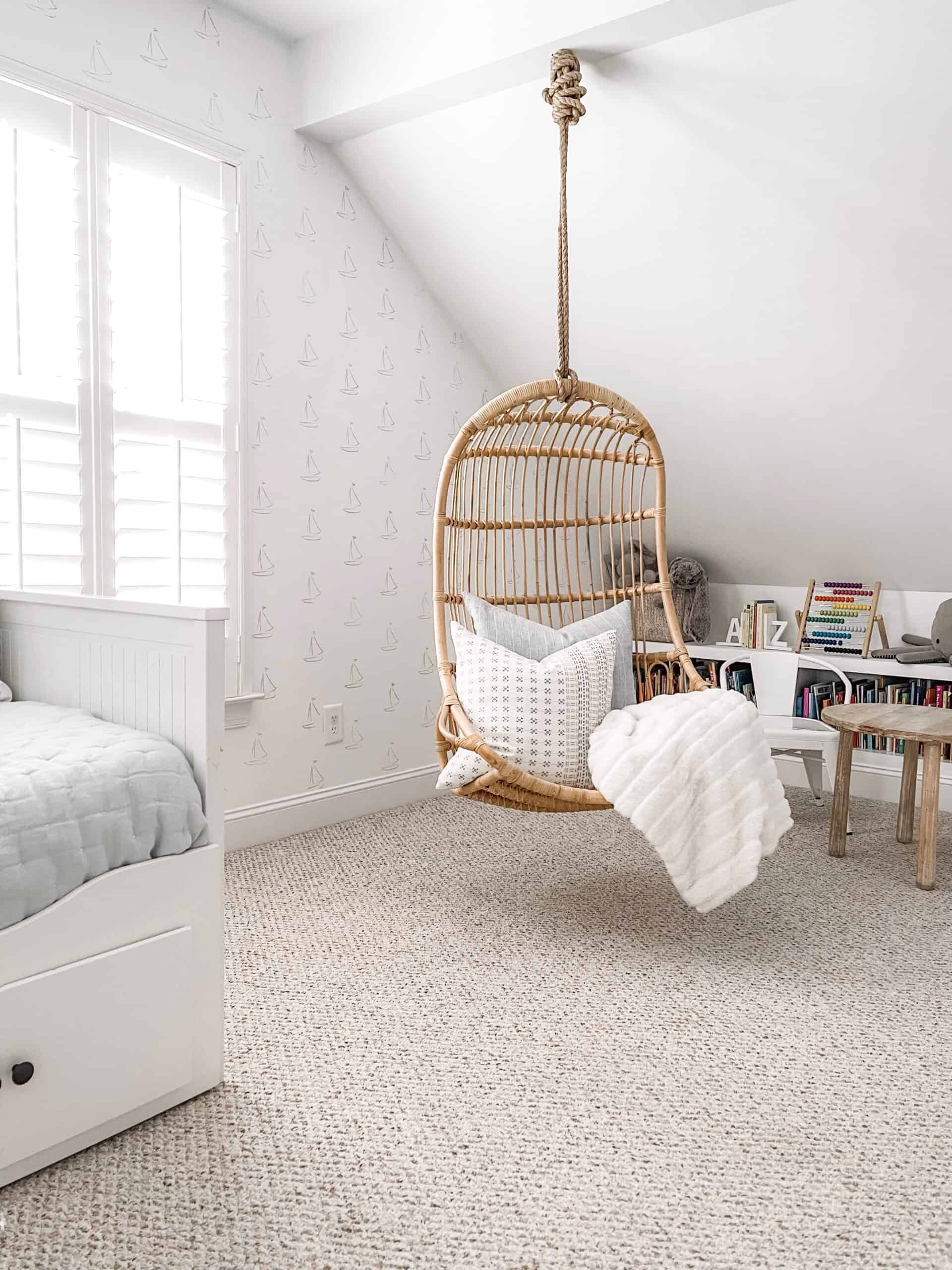 Blue and white play room with a hanging rattan chair from Serena & Lily