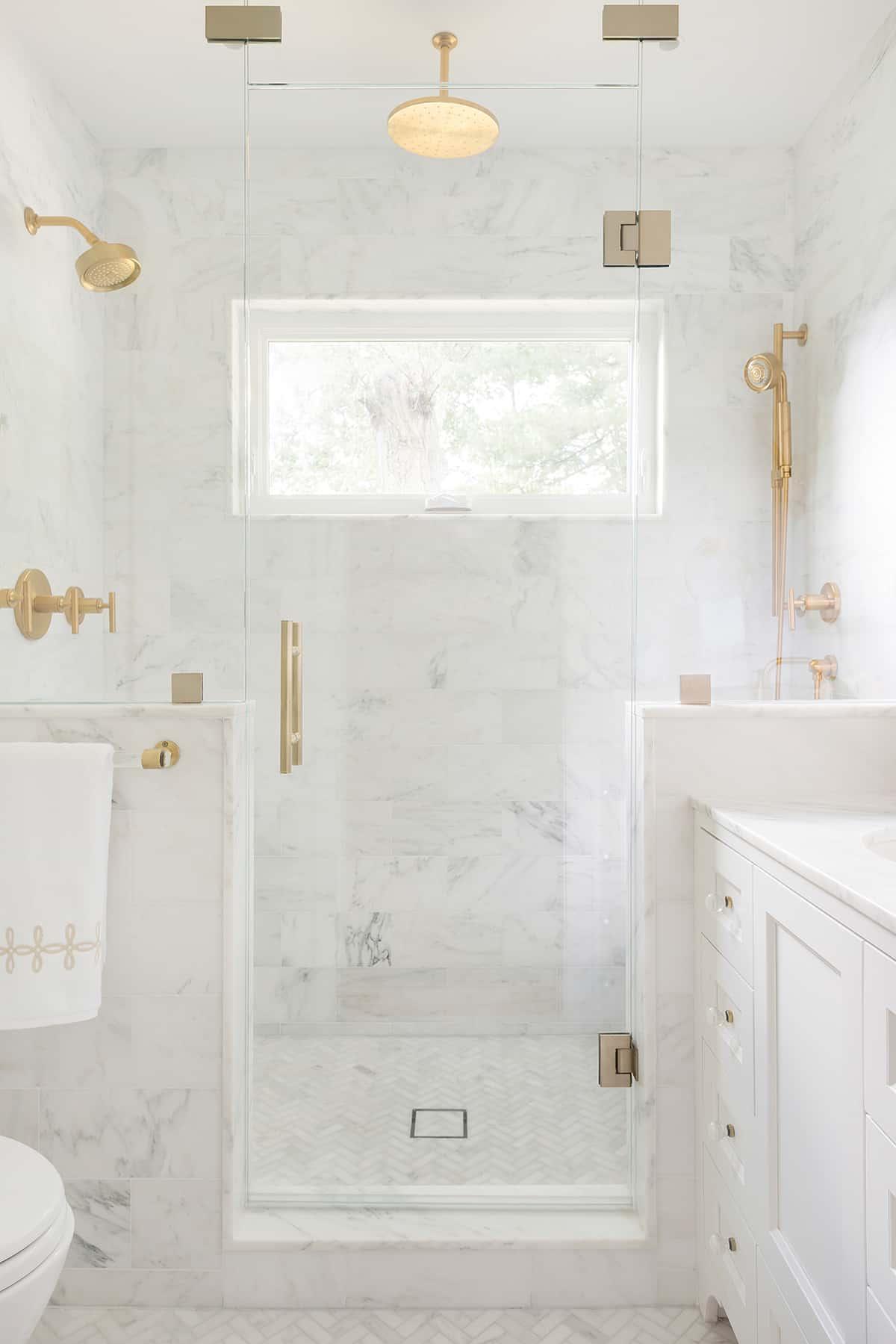 Timeless marble design in bathroom with herringbone floor.
