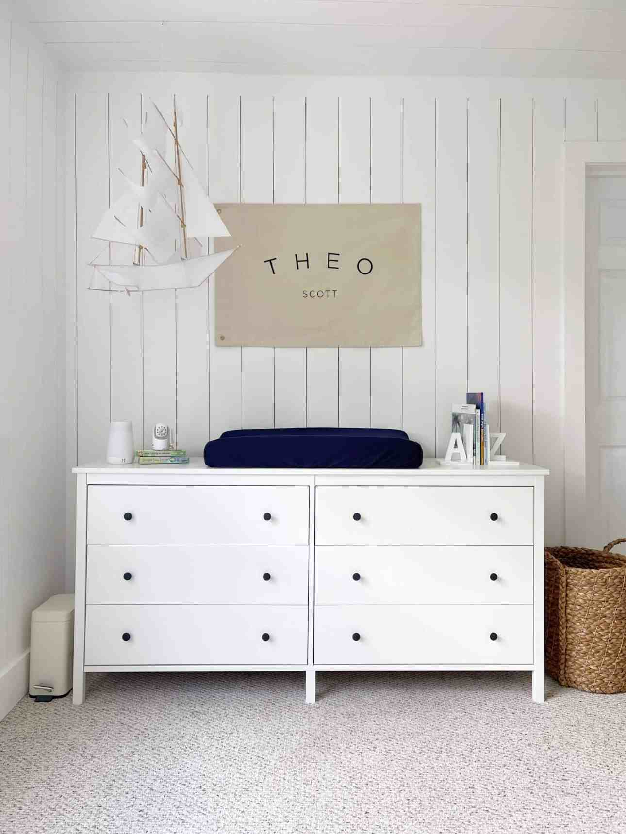 Vertical shiplap room with changing table and hanging ship.