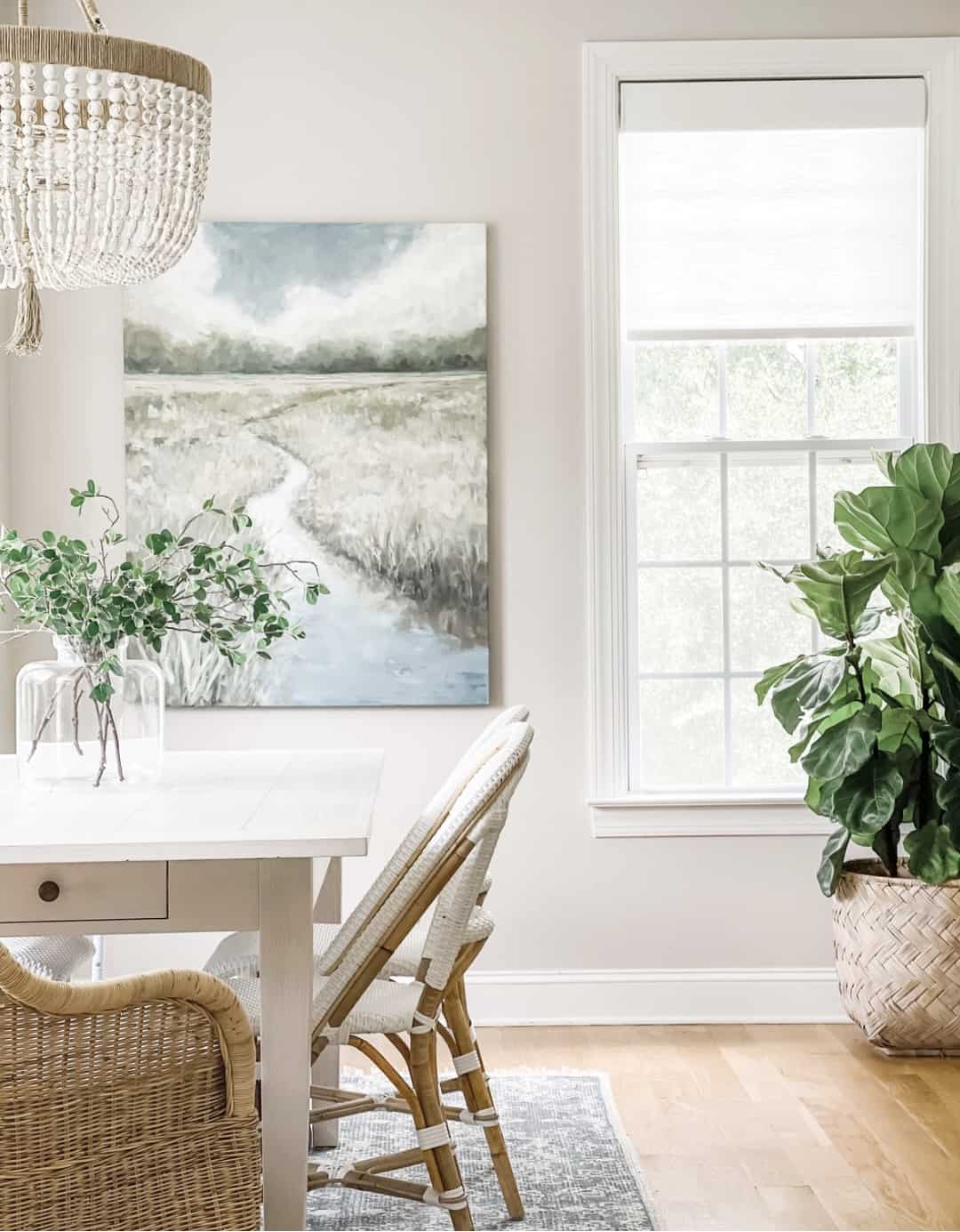 Serena & Lily breakfast nook with coastal art, bistro chairs, and an expandable dining table.