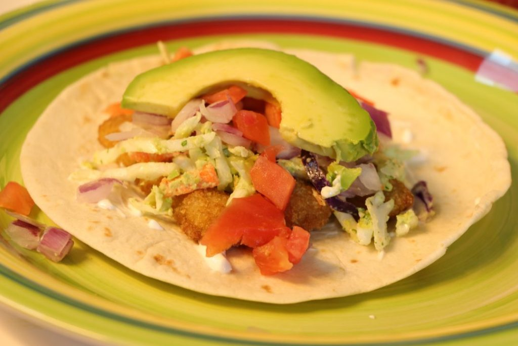 Fish taco with avocado and cilantro slaw