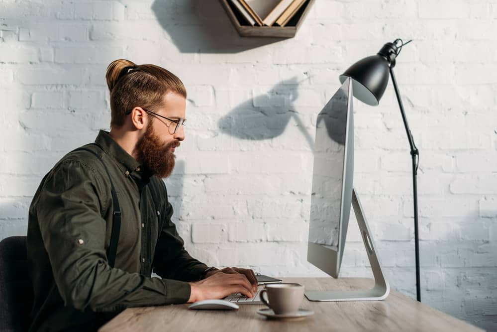 Side view of handsome businessman using computer