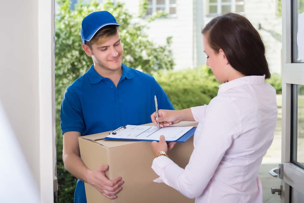 Woman Signing Receipt Of Delivery Package