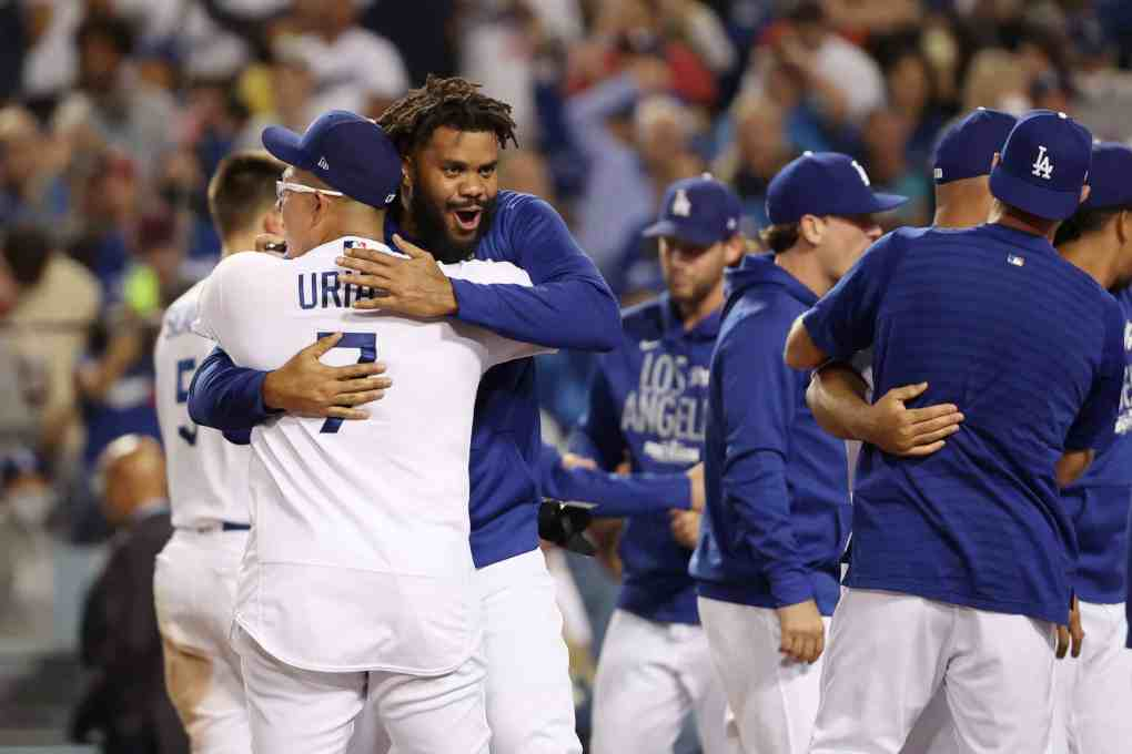 Kenley Jansen #74 and Julio Urias #7 of the Los Angeles Dodgers celebrate their 3 to 1 win over the St. Louis Cardinals during the National League Wild Card Game at Dodger Stadium on October 06, 2021 in Los Angeles, California.