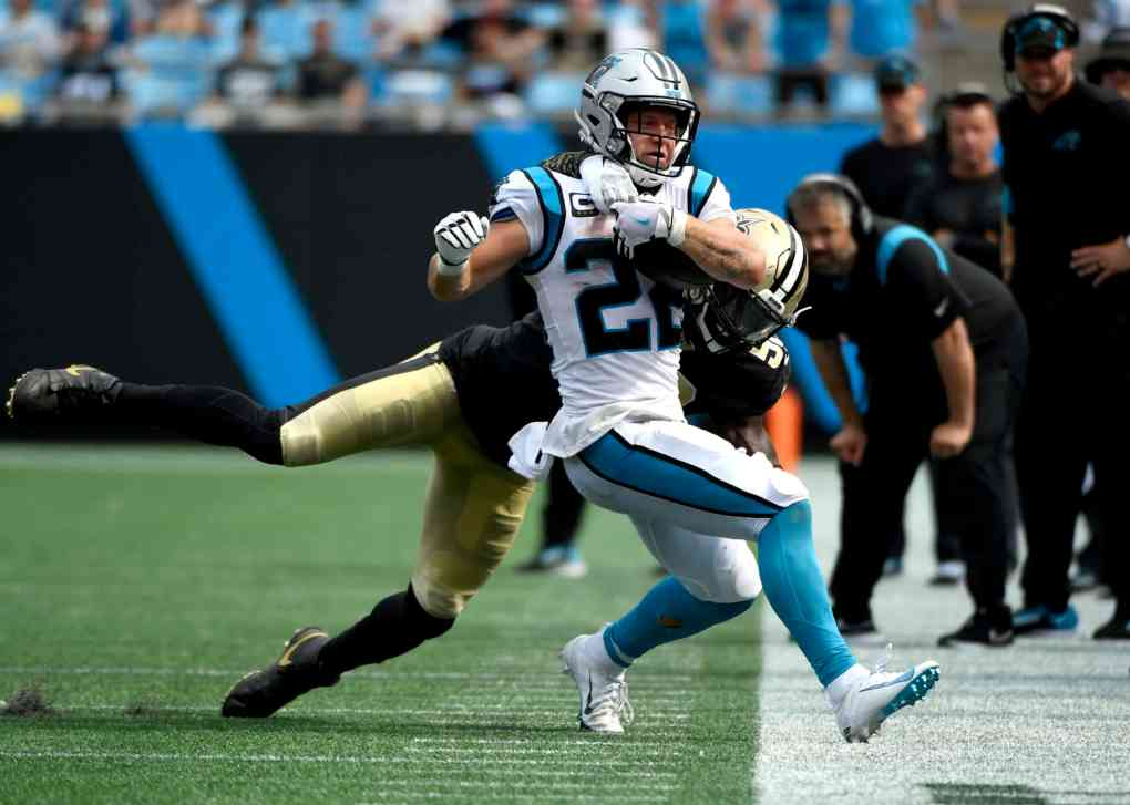Running back Christian McCaffrey #22 of the Carolina Panthers is tackled by outside linebacker Demario Davis #56 of the New Orleans Saints at Bank of America Stadium on September 19, 2021 in Charlotte, North Carolina.