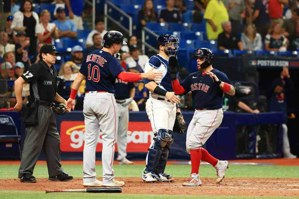 Hunter Renfroe #10 and Christian Vazquez #7 of the Boston Red Sox celebrate scoring on a two RBI single by Enrique Hernandez #5 in the ninth inning against the Tampa Bay Rays during Game 2 of the American League Division Series at Tropicana Field on October 08, 2021 in St Petersburg, Florida.