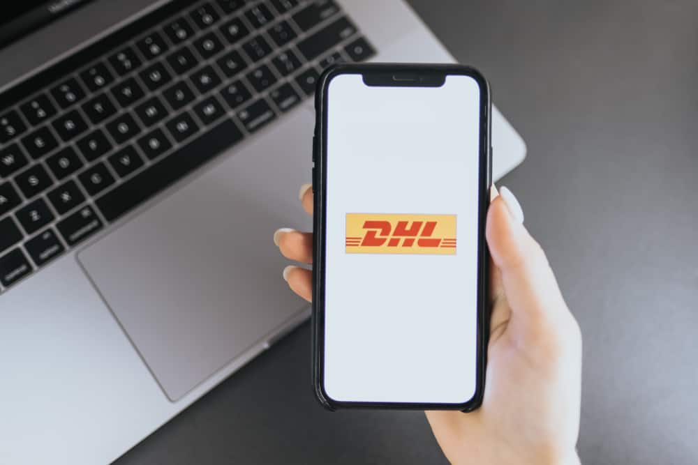 hand holding iPhone X with DHL logo on the screen