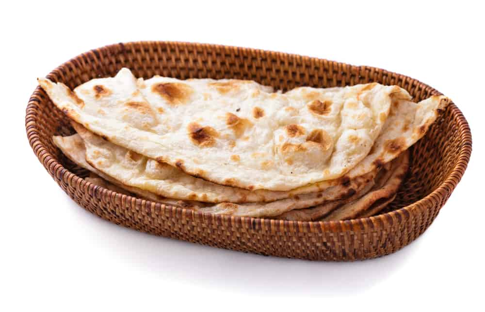 stack of indian naan bread in small basket