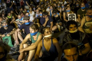 "Demonstrators with their mouths taped sit outside the Spanish parliament during a protest against Spanish government's new security law in central Madrid, Spain, early July 1, 2015. Spanish government's new security law, which toughens fines for unauthorised street protests, comes into effect July 1. Critics consider it a violation of the right to protest and a limit to free expression and have labeled it ""Ley Mordaza"" (Gag Law). REUTERS/Juan Medina - RTX1IIKE"