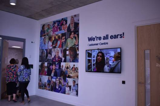 "Tesco room pictures on wall of people and ""we're all ears"""