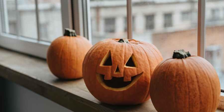 pumpkins and jack o lantern next to a window