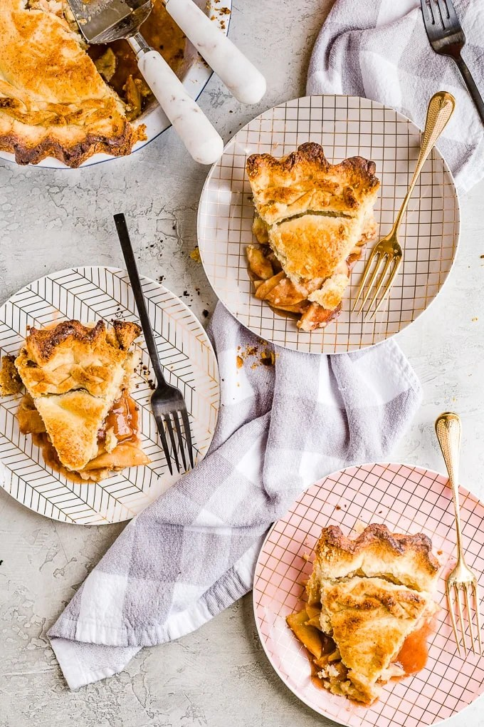 3 slices of homemade apple pie on small plates with forks