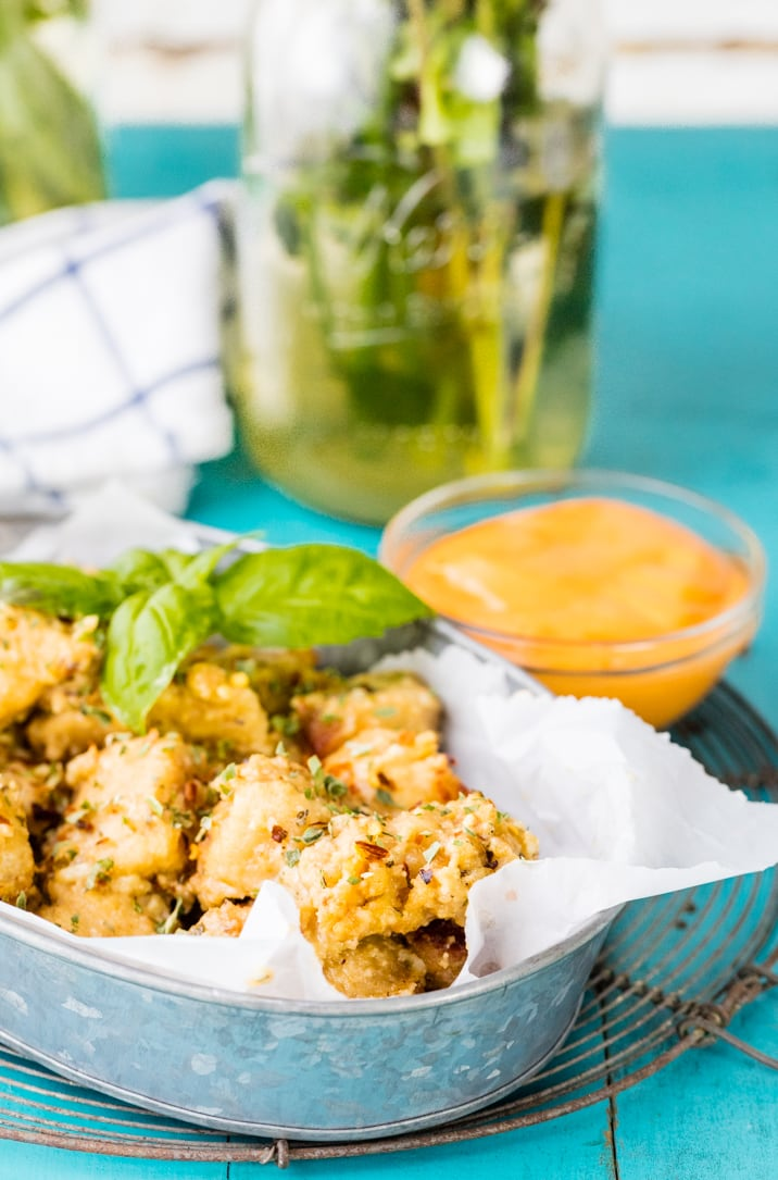 a basket of crockpot chicken wings with a bowl of dipping sauce
