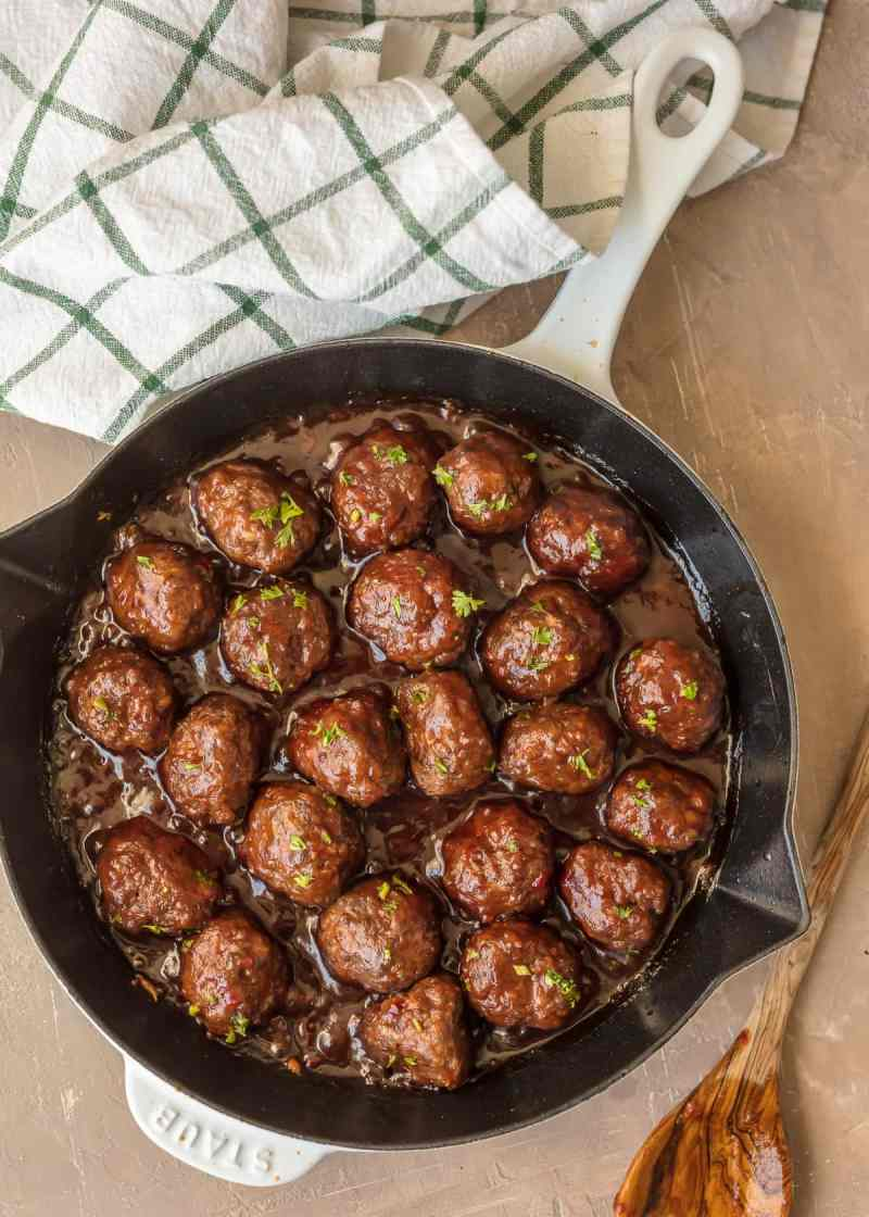 Cocktail Meatballs in a skillet, covered in cranberry sauce